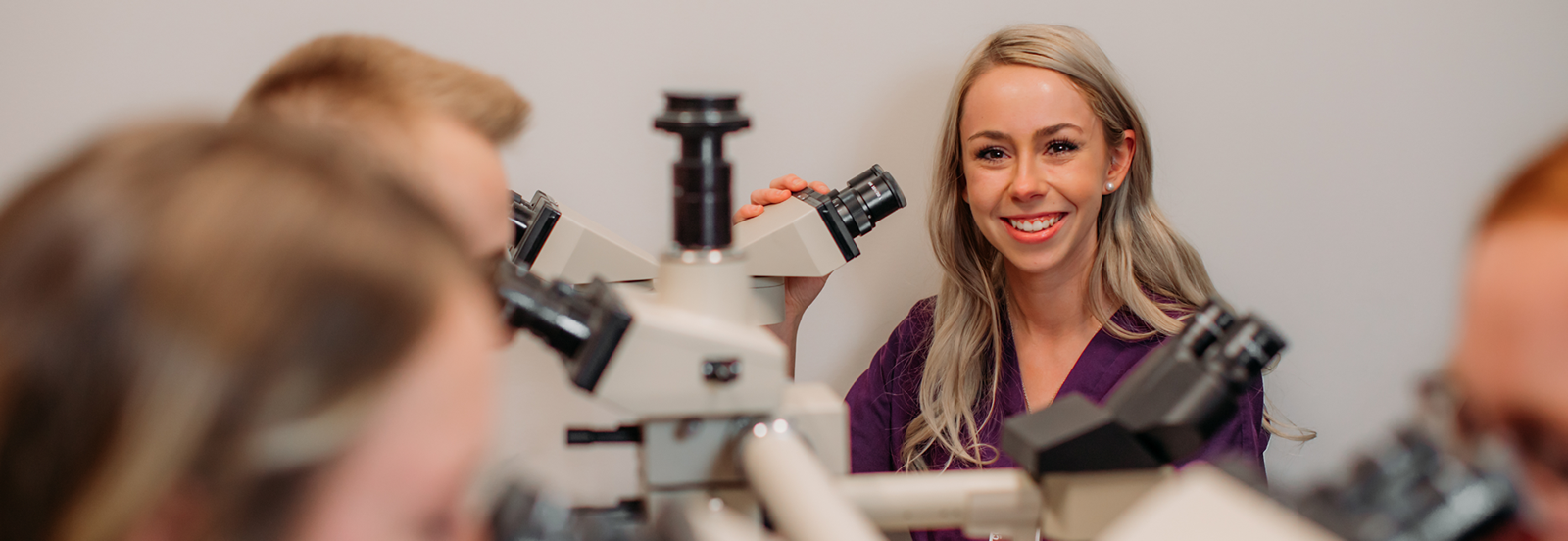 Mercy College student smiling with microscope