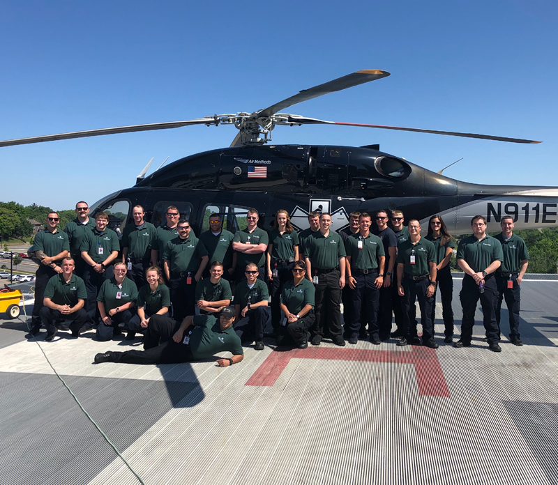 Emergency Medical Services students next to emergency helicopter